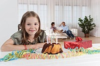 Germany, Munich, Girl with birthday cake, parents in background