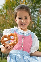 Germany, Bavaria, Huglfing, Girl holding pretzel in garden, smiling, portrait