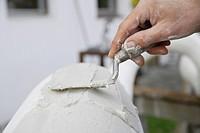 Germany, Upper Bavaria, Munich, Schaeftlarn, Sculptor applying plaster with trowel