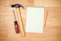 Pad of Paper, Pencil, Hammer and Screwdriver on a Wood Background.