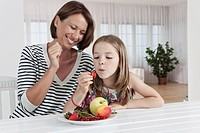 Germany, Munich, Mother and daughter eating fruits, smiling