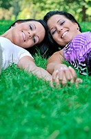 Togetherness _ two smiling happy sisters lying in grass outdoors and holding hands with copy space