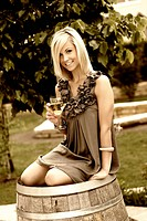 beautiful young woman with glass of wine sitting on wine cask