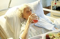 Elderly woman lying in a sickbed, drinking from a mug, in front of her a plate of food.