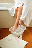 young adult woman does a footbath _ pedicure _ in the bathroom