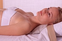 Woman treating her neck with an hayflowers back against muscle pains