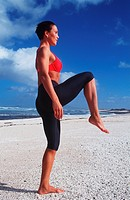 Young adult woman stands at the beach and does doing sports practice