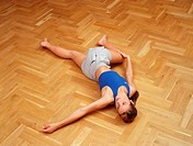 Young adult woman does in a stretching_practice hall _ supine position