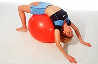 Young adult woman does doing sports practices with a red Exercise ball _ supine position