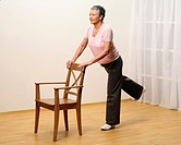 older woman doing gymnastics with a chair _ sprawel leg to the back _ muscularity _ senior