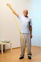 older man is training his shoulders with a stretch_band _ muscularity _ senior