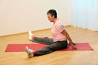 older woman doing floor exercise on a mat _ senior is doing gymnastics fŸr better flexibility _ straddle position _ to lean forward with straight back