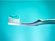 Toothbrush with turquoise toothpaste in front of blue background