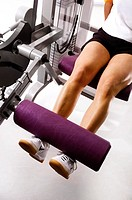 Woman at strength practice with the legs in the gym
