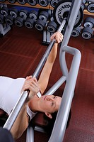 young woman in a fitness center weight lifting