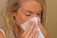sneezing young woman with a tissue