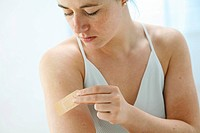 young woman is sticking a plaster on her upper arm _band_aid