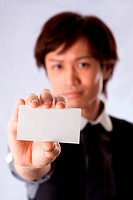 Blurred Asian business man holding and presenting a blank white card. Sales representative introducing himself.