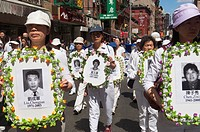 Carrying banners and signs members of Falun Dafa Falun Gong from around the world parade through the streets of Chinatown in New York Practitioners of...