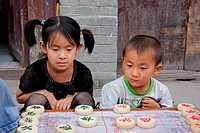 A Chinese boy and girl watching a board game on the streets of HoHot, Inner Mongolia, northern China