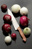 Variety of red and white onions with knife