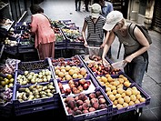 Women choosing fruit outside a grocery store.