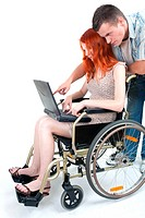 man, woman keeping laptop on wheelchair