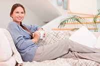 Beautiful woman holding a cup of coffee in her living room