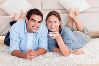 Cute couple watching TV while lying on a carpet in their living room