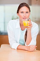 Portrait of a woman drinking juice in her kitchen