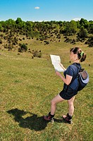 Young woman in nature looks to map and wants to find way