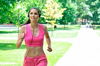 Young person woman with headphones listening music running outdoors in park on sunny day