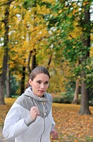 Young person woman running outdoors in park on cold autumn day