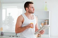 Young man drinking orange juice while reading the news in his kitchen
