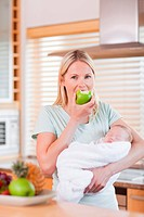 Young mother with newborn on her arms having an apple
