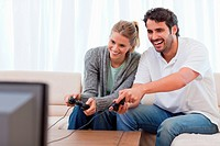 Couple playing video games in their living room