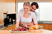 Couple eating fruits in their kitchen