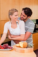 Portrait of a couple eating fruits in their kitchen