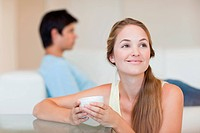 Woman having a tea while her fiance is sitting on a sofa in their living room