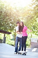 Young multi racial couple skateboarding