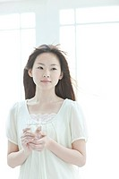 Young woman holding glass of water