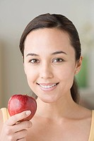 Portrait of attractive woman holding apple