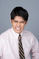 Portrait of young businessman pulling funny faces