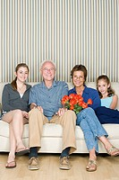 Portrait of grandparents with two granddaughters 8_9, 14_15 sitting together on sofa