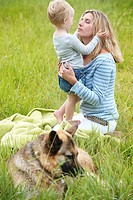 Mother and son sitting in grass with dog