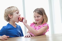 Children eating apple in kitchen