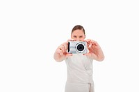 Young businesswoman taking a picture against a white background