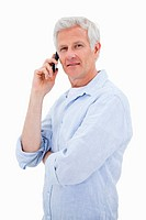 Portrait of a man making a phone call while looking at the camera against a white background