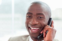 Close up of a cheerful businessman on the phone in his office