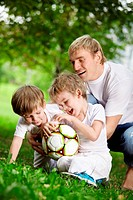 Father and two sons play football in a summer garden